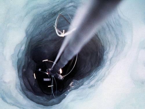 Подледная рыбалка. Ученые опускают в отверстие глубиной около 2км в ледяном панцире Антарктиды трос с прикрепленными к нему чувствительными фотодетекторами, которые образуют нейтринный телескоп AMANDA (Antarctic Muon and Neutrino Detector Array). Земной шар служит защитным фильтром для этого телескопа, регистрирующего нейтрино из глубин космоса. Изображение: «Популярная механика»