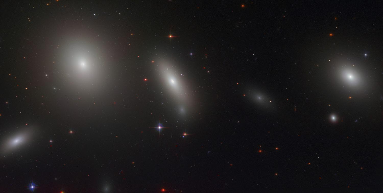 Линзовидная галактика NGC 1277 (немного левее центра изображения) и ее  соседи по скоплению Персея. В центре этой галактики находится одна из самых  массивных ...