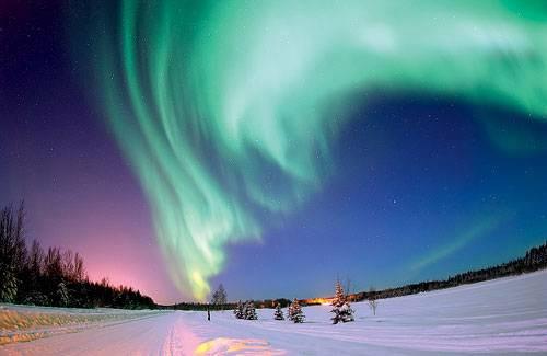 Полярное сияние порождается взаимодействием атмосферы и заряженных частиц, захваченных магнитным полем Земли, которое в приполярных областях перпендикулярно поверхности. Изображение: «Популярная механика»